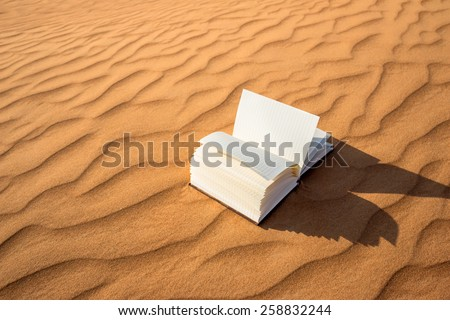 Open notebook stranded in the golden desert dunes during sunset  - stock photo