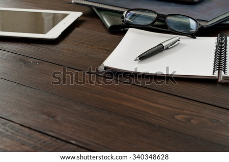 Open notebook, tablet computer, glasses and folders on the office table. Copy space. Free space for text. Top view - stock photo