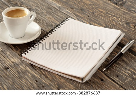 Open notebook with a pen and a cup of espresso coffee on a dark wooden surface