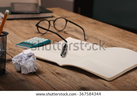 Open notebook with a pen and calculator on wooden table home in the evening - stock photo