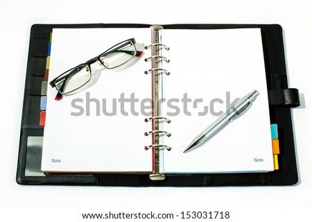 Open notebook with ballpoint pen ant glasses. - stock photo