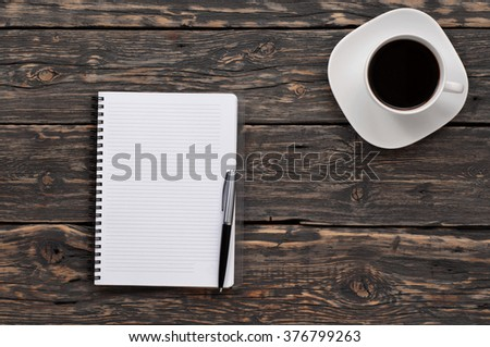 open notebook with blank pages and a cup of black coffee on a dark vintage wooden table, top view