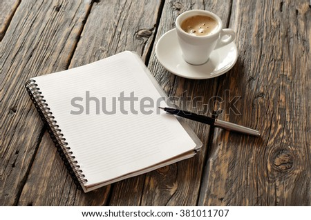 open notebook with blank pages and pen with cup of coffee espresso on the dark wooden surface, top view