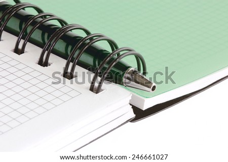 Open notebook with blank pages and with green pen, isolated on white background