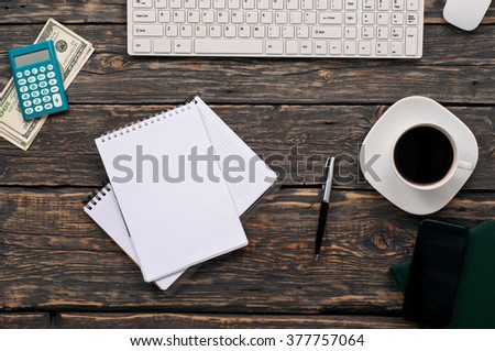 Open notebook with blank pages on home office desk with pen, calculator, keyboard, money, and coffee, top view - stock photo
