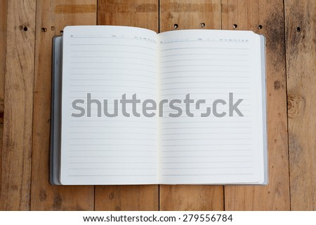 open notebook with blank pages on wood table - stock photo