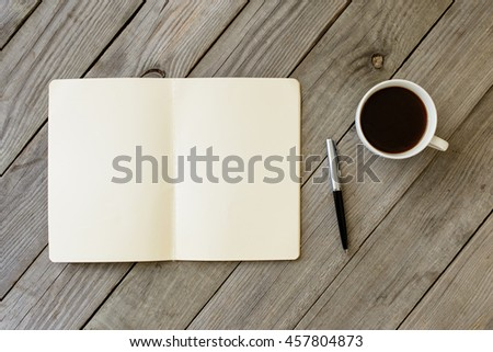 Open Notebook With Blank Pages, Pen And Cup Of Coffee On Wooden Table. Top View