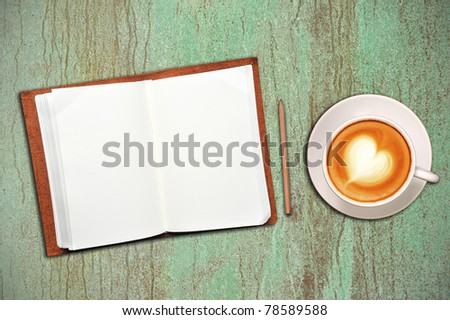 Open notebook with cup of coffee on green and brown background