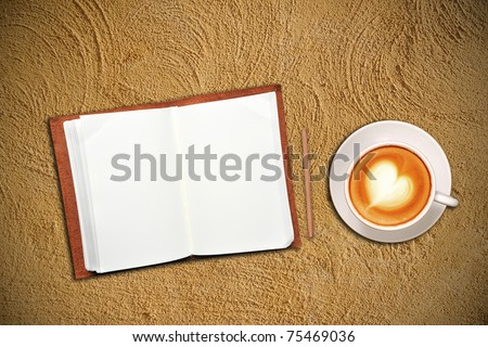 Open notebook with cup of coffee on sand