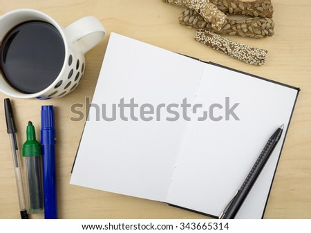 Open notebook with pen, a cup of coffee and some batons with seeds, on wooden surface. - stock photo