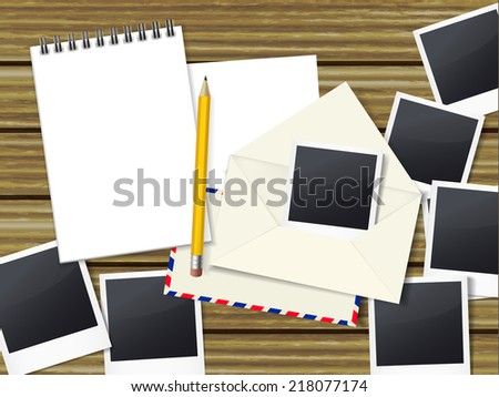open notebook with pen and lots of photos on wooden table - stock photo