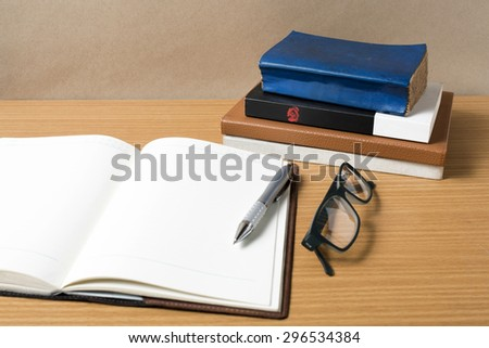 open notebook with stack of book on wood background