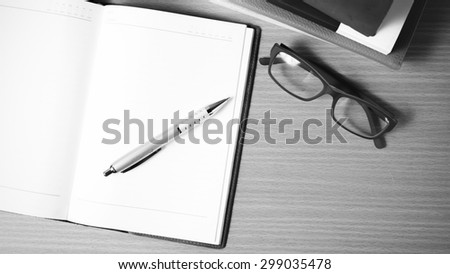 open notebook with stack of book on wood background black and white color tone style