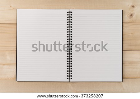 Open notebook with white lined pages on wooden office desk .Top View