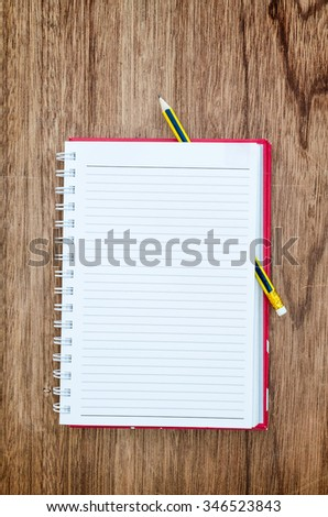 Open notepad and pencil on wood table