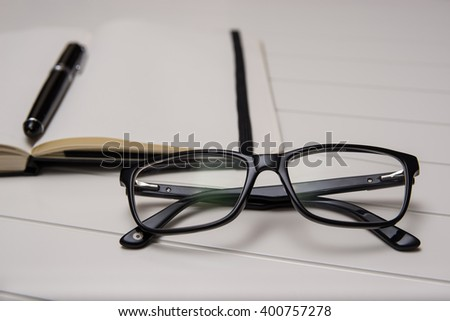 Open notepad - daily planner with leather cover and black vintage pen on a white table with glasses