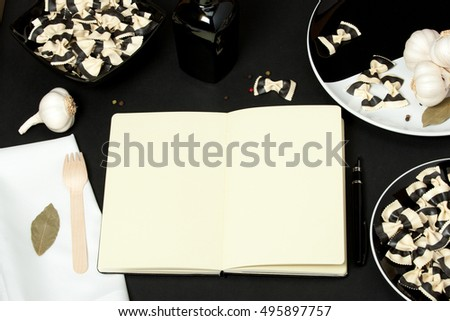 Open Notepad With Blank Pages. Italian Farfalle Durum Wheat Pasta With Cuttlefish Ink. Black And White Plates.