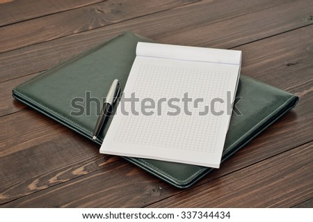 Open notepad with blank pages with a pen on the leather business folder on the office desk close up. Top view - stock photo
