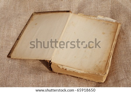 Open old book on burlap background. - stock photo