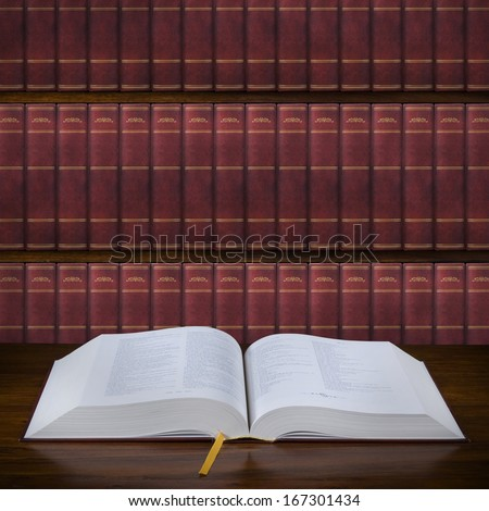 Open old book on the table and bookshelf in the background - stock photo