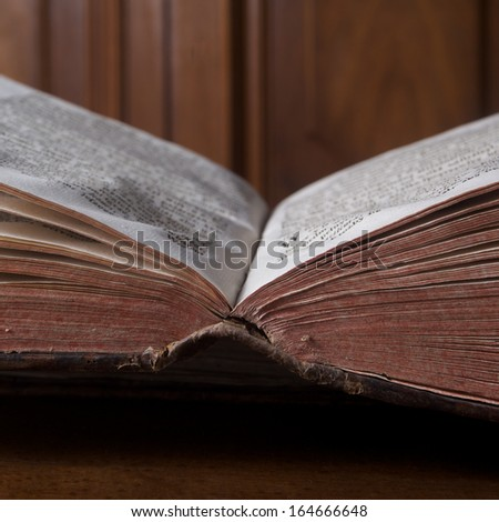 Open old book on wooden background