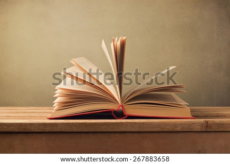 Open old book on wooden table - stock photo