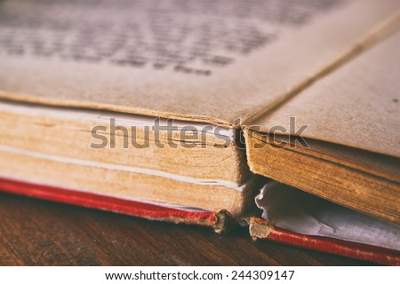 Open old book over wooden table. macro image with selective focus