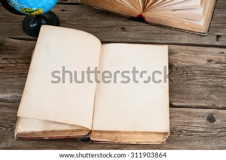 open old book with blank pages on wooden table with globe close up. Copy space. Free space for text - stock photo