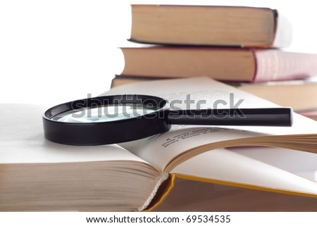 Open old book with loupe on white background. Isolated. - stock photo