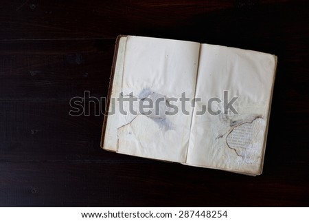Open old vintage book on dark wood background - stock photo