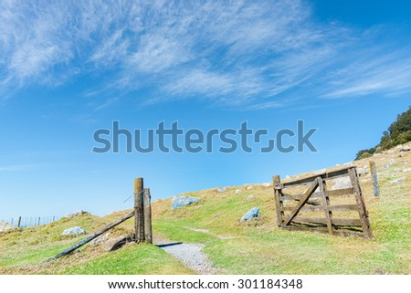 Open old wooden farm gate on hillside under blue sky with light wispy clouds - stock photo