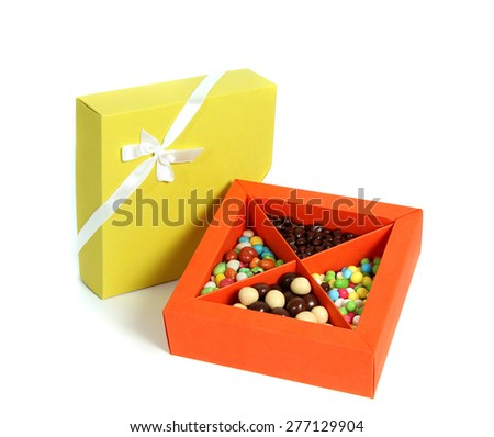 Open orange box full with candy and closed yellow box with ribbon on white background. - stock photo