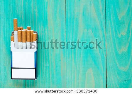Open pack of cigarettes on blue wooden background with copy-space - stock photo