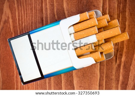 Open pack of cigarettes with the filter on brown table
