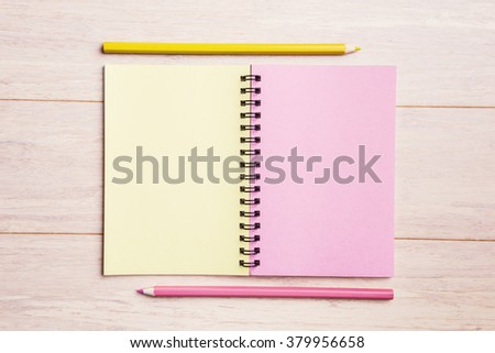 Open pad with pink and yellow pencils