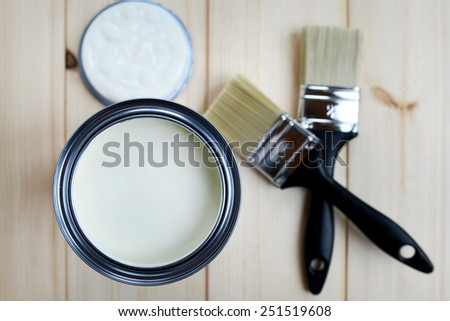 Open Paint Can Milky White Colour and Brushes on Wooden Background  - stock photo