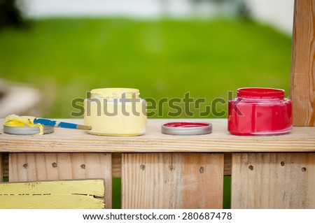 Open paint containers on a wooden booth - stock photo