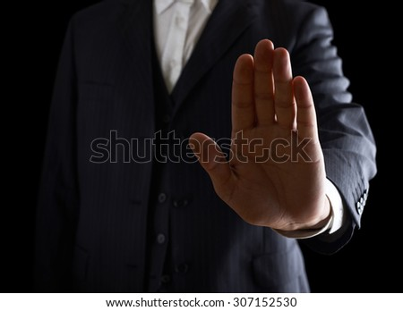 Open palm stop sign close-up shot of a caucasian man in a business suit, low-key dramatic light composition - stock photo