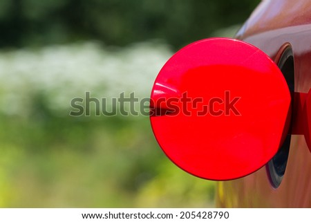Open petrol cap cover on red automobile  - stock photo