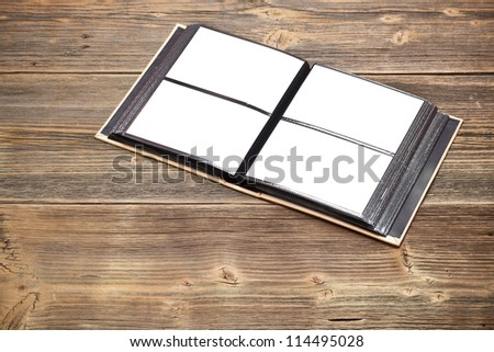 Open photo album book on old wooden table - stock photo