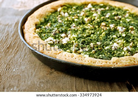 Open pie with spinach on wooden table close up - stock photo
