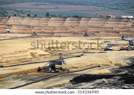 open pit coal mine with machinery and excavators - stock photo