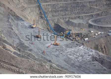 Open pit mine with ore conveyor - stock photo