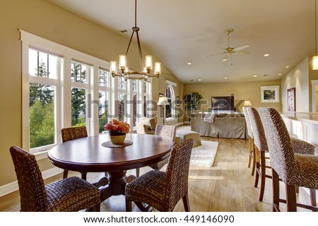 Open plan interior with lots of space. View of dining room and living room. Has vaulted ceiling, hardwood floor and large six pane window.