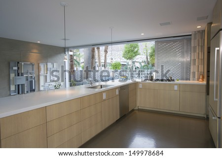 Open plan kitchen furnished in light wood at home - stock photo