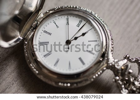 open pocket watch and chain lie on a light wooden table background - stock photo