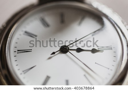 open pocket watch and chain lie on a light wooden table background, arrow on the clock