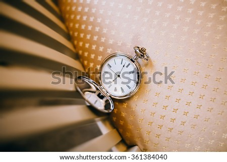 Open pocket watch on an old chair - stock photo