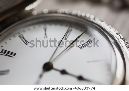 open pocket watches lie on a light wooden table background, arrow on the clock, arrows on pocket watches show time of day, dial with roman numerals  - stock photo