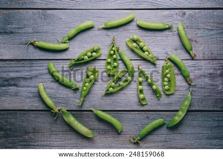 Open pods of ripe fresh green peas on wooden background, top view - stock photo